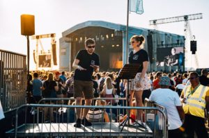 British Sign Language Interpreters signing a performance at the main stage to people from the viewing platform while the sun sets